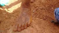 With mud covered foot