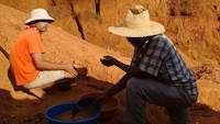 Mr. Louis advising the mining site owner about gold panning methods