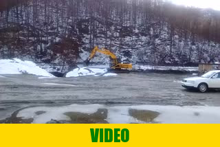 Excavator digging soil from the stream