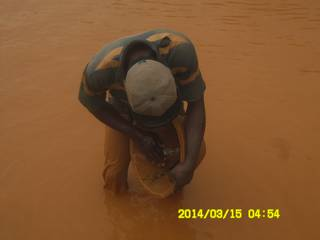 Miner panning for gold with traditional wooden bowl in Ghana