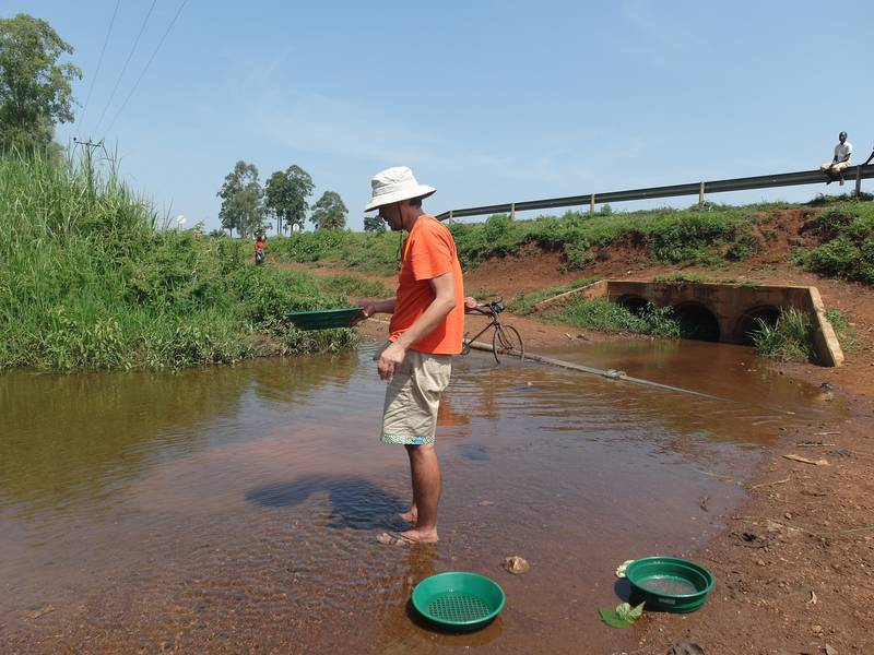 Mr. Louis gold panning soil samples in Uganda