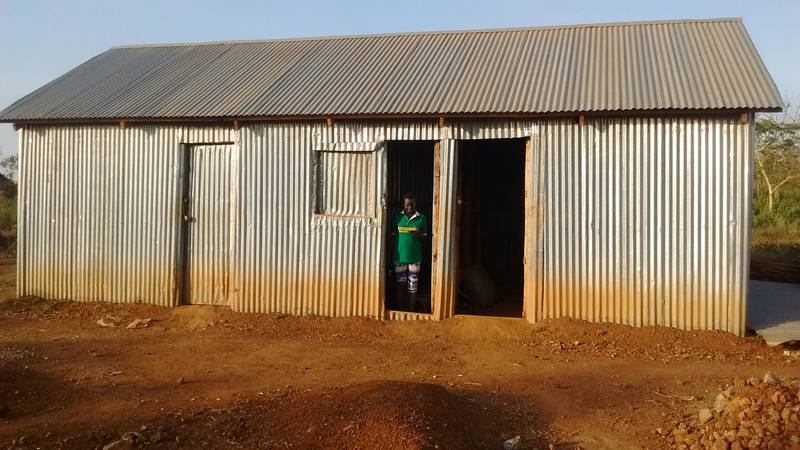 Goldivanti LP purchasing manager in Uganda in front of the storage room