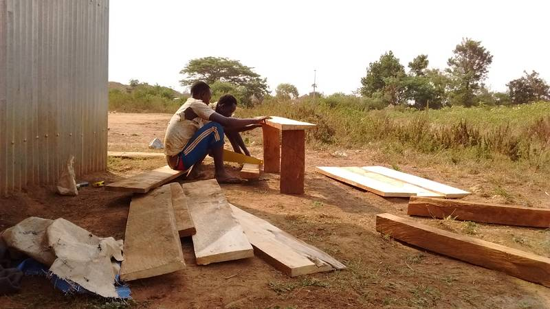 Workers preparing bench and desks as open-air furniture