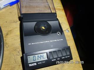 0.144 grams of natual gold particles on the balance scale