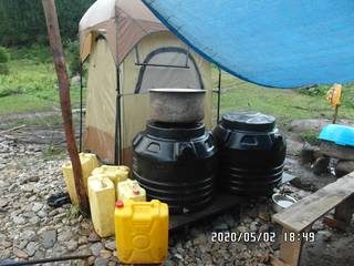 2020-05-02: Water tanks used as storage for food and shower tent in background