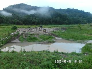 2020-05-02: Mining pit covered with water with Bwindi Impenetrable Forest in background