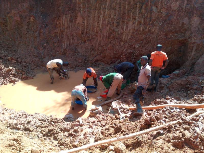Ugandan miners panning for a rich gold ore